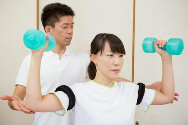 症状の再発予防のため、腕の加圧トレーニングをする女性と、指導する院長