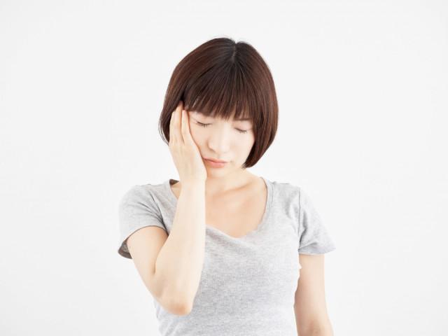 顔面神経麻痺で顔をさえる女性