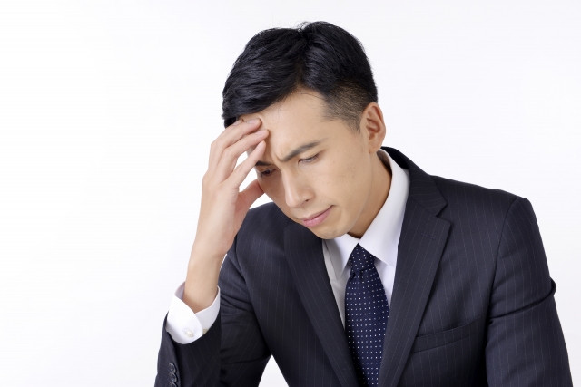 仕事のストレスや緊張から解放され血管が拡張したために片頭痛に襲われる男性